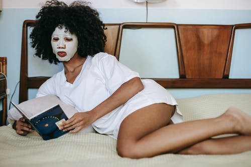 Young ethnic female in white t shirt relaxing on bed and reading book while doing facial routine with cosmetic sheet mask on face