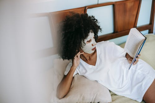 Young ethnic female in white t shirt with facial cosmetic mask on face having rest on bed and reading book