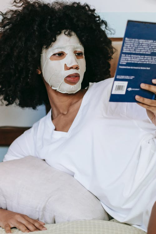 Woman relaxing on bed with book while doing cosmetic procedure