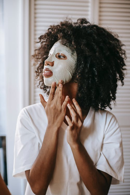 Young ethnic female with curly hair standing in room and placing facial sheet mask on face
