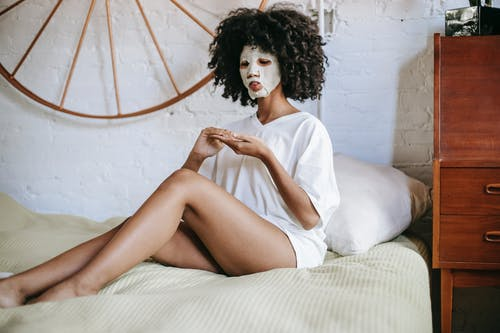 Young ethnic female with curly hair and with cosmetic mask on face sitting on bed and doing skincare routine in bedroom