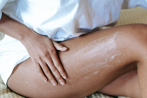 Woman massaging leg with lotion in bedroom