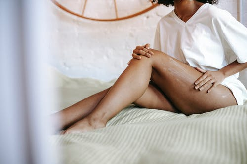 Side view of unrecognizable female in white t shirt sitting on bed and applying lotion on leg while resting in weekend