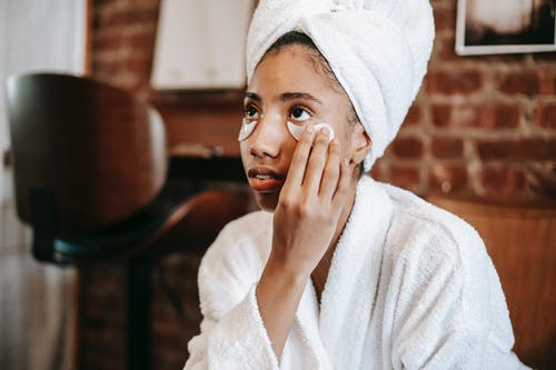 Young African American female with towel on head applying eye patches on face while looking away