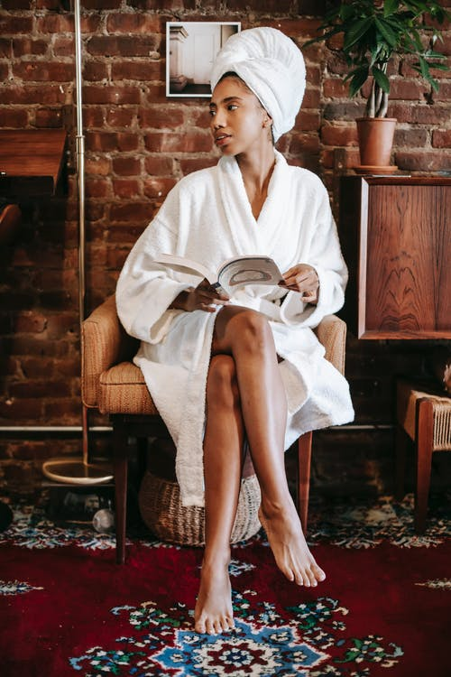 Young African American female in white robe and towel sitting on chair with book while resting in cozy room