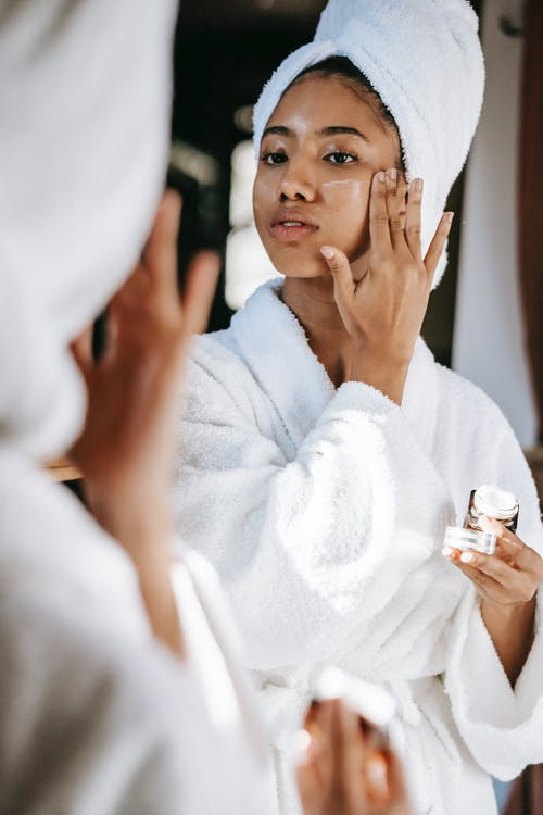 Young black female  in white robe and towel on head  applying moisturizing cream on face while standing in bathroom