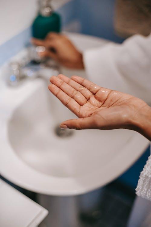 Crop woman showing soap in bathroom