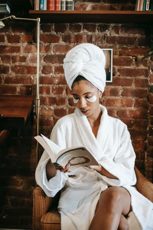 Ethnic female in turban and white robe sitting in armchair and reading book during morning skin care routine