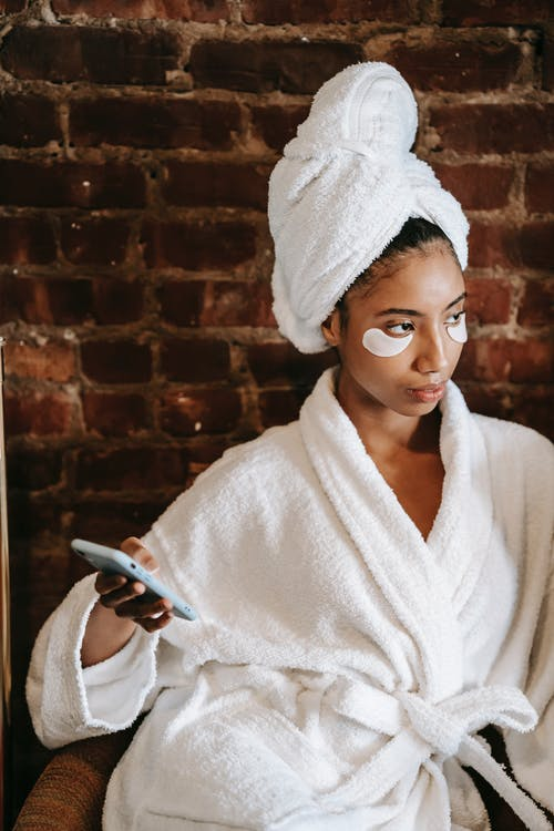 Serious ethnic woman with cosmetic patches using smartphone