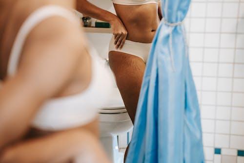 Ethnic woman showing body curves in bathroom