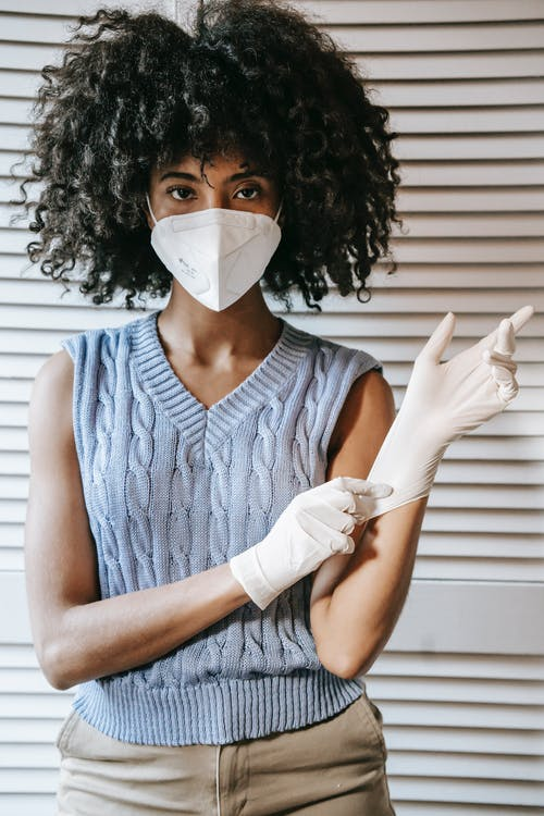 Serious ethnic female with curly hair in mask adjusting protective gloves during covid epidemic