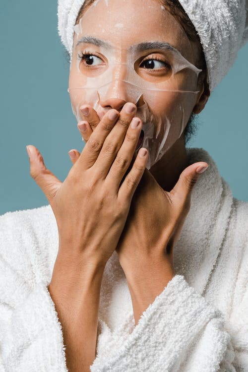 Amazed young ethnic woman covering mouth with hands during skin care routine