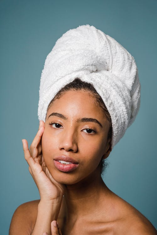 Alluring young black female touching face and looking at camera after shower