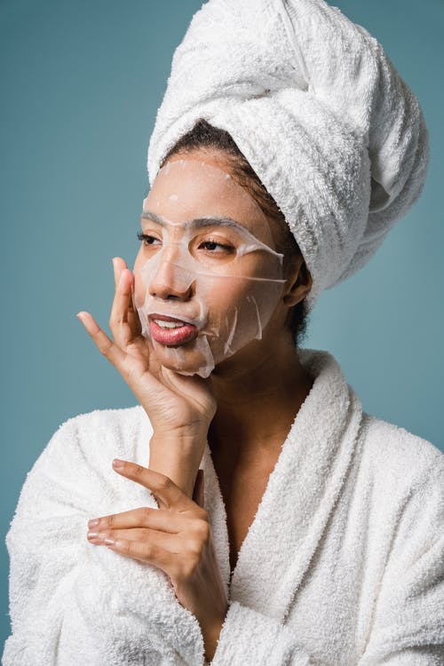 Smiling young ethnic female applying sheet mask on face after shower