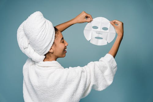 Back view of happy young African American female in bathrobe with towel on head smiling while demonstrating skin care mask against blue background