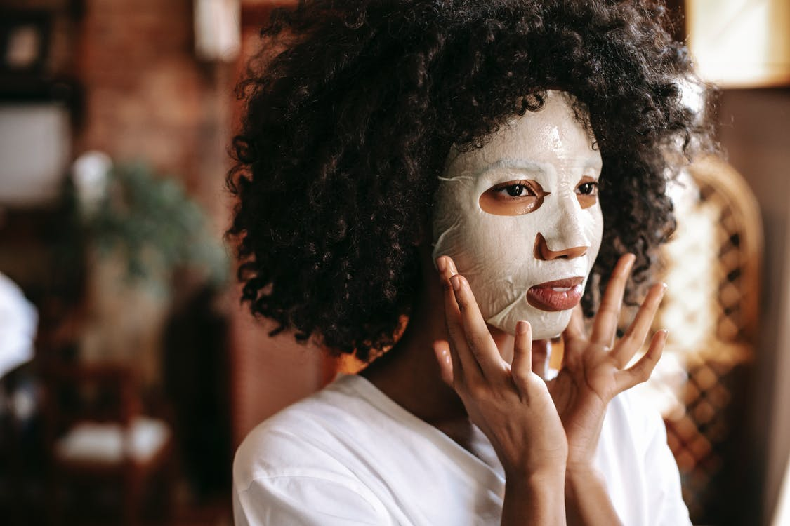 Calm young African American lady with curly hair applying moisturizing sheet mask while relaxing alone at home