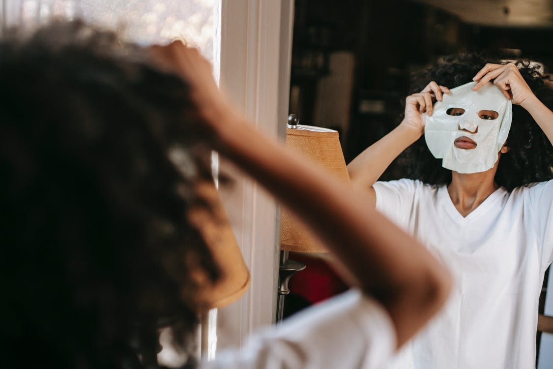 Concentrated African American female in domestic cloth putting moisturizing sheet mask while standing near mirror at home in daylight