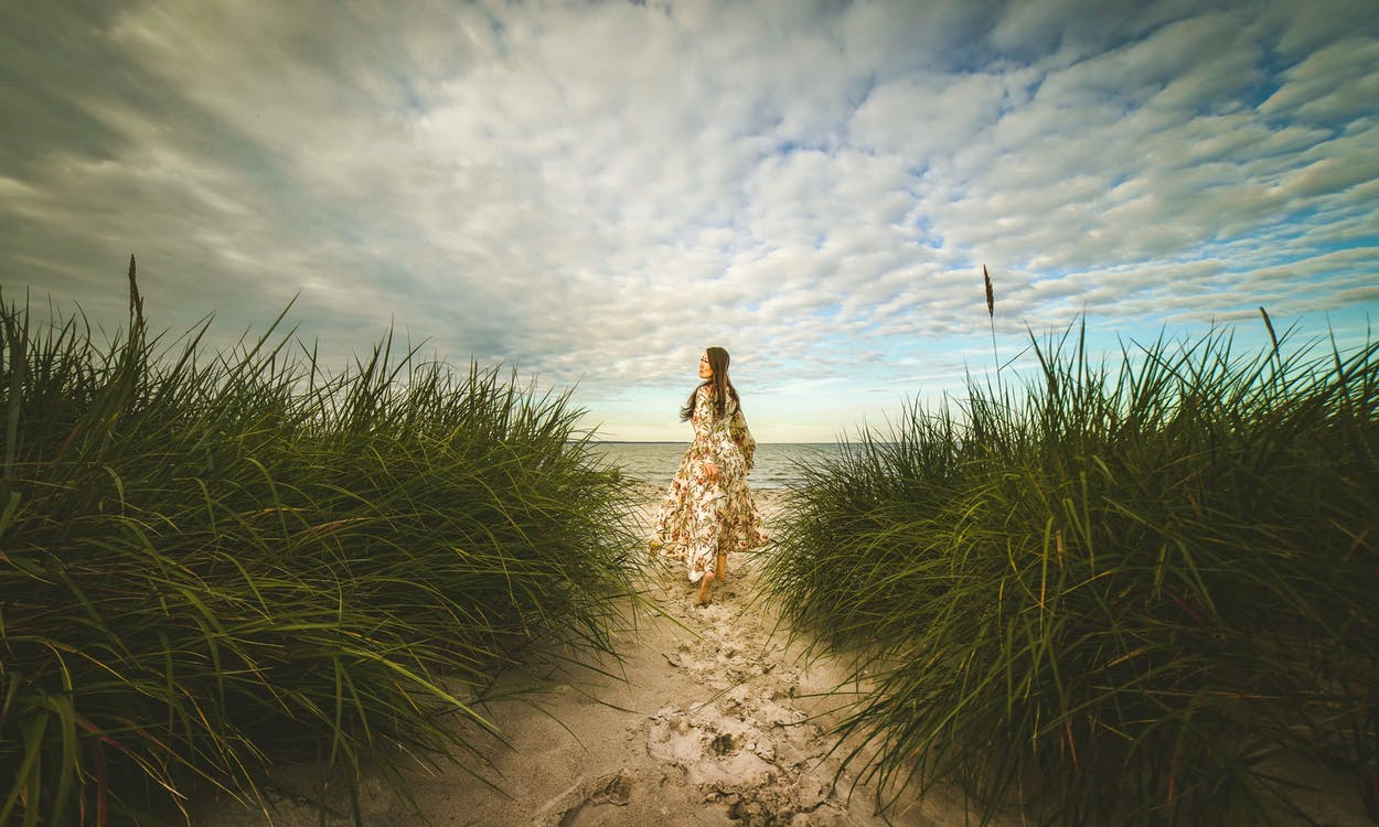 Woman in Brown Dress Standing on Brown Sand Under White Clouds