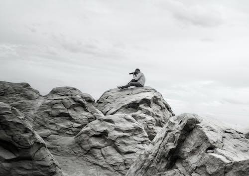 Man Taking Photos Sitting on Rocky Mountains