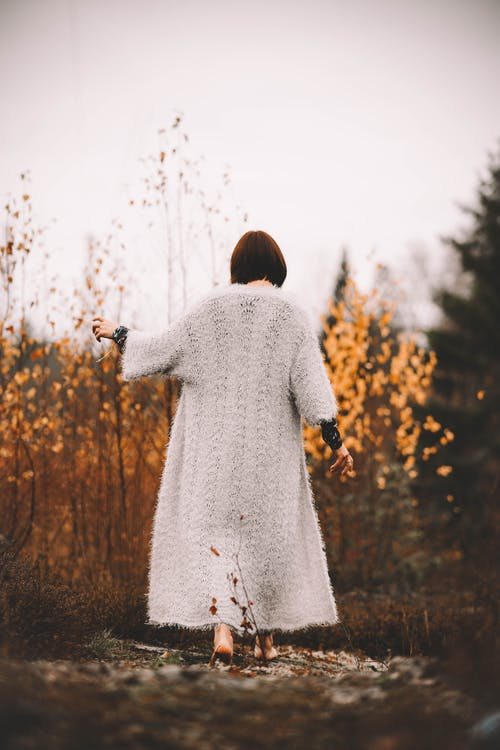 Woman in White Knit Sweater Standing on Brown Grass Field