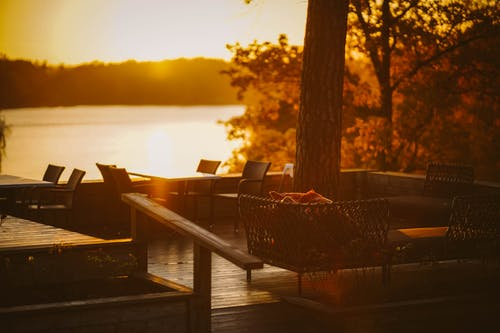 Brown Wooden Table and Chairs Near Body of Water during Sunset