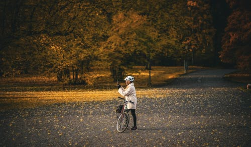 Man in White Long Sleeve Shirt Riding Bicycle on Road
