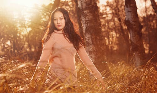 Woman in Brown Turtleneck Sweater Standing on Brown Grass Field