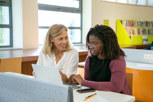 Positive adult female teacher explaining task to young black student with Afro braids doing assignment on laptop in modern classroom