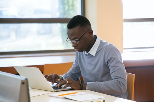Concentrated young African American male student in formal clothes and eyeglasses reading notes in planner and typing on laptop while doing assignment in modern workspace