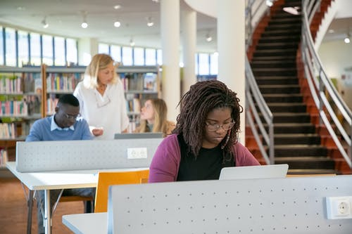 Concentrated young diverse students using laptops during lesson in library