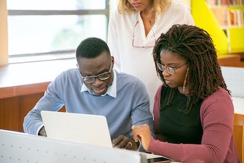 Anonim öğretmenle Sınavlara Hazırlanırken Dizüstü Bilgisayar Kullanan özenli Genç Siyah Grup Arkadaşları