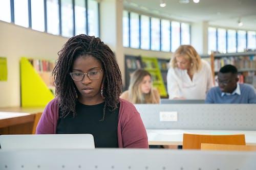 Öğretmenle Birlikte Kütüphanede Sunum Yapan çok ırklı öğrenciler