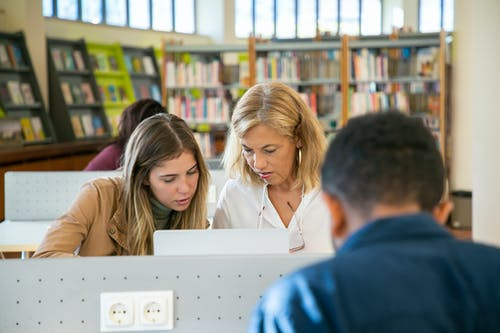Focused student preparing university project with teacher