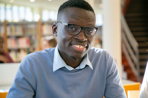 Positive African American male learner with toothy smile in eyeglasses sitting in library