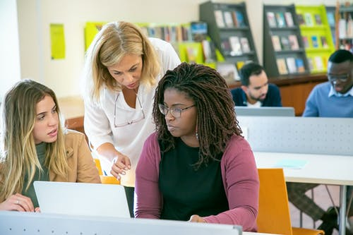 Group of multiracial students studying in library with teacher