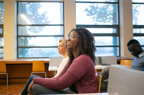 Side view of positive African American female student sitting on chair near professor and classmate while listening information attentively