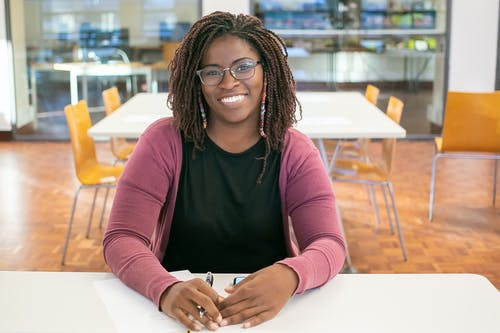 Cheerful black woman in glasses sitting at table in university