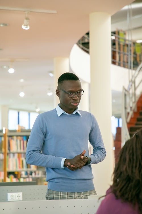 Black student standing in front of audience in library