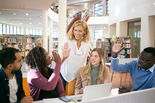 Позитивные многонациональные студенты празднуют успех в проекте с учителем