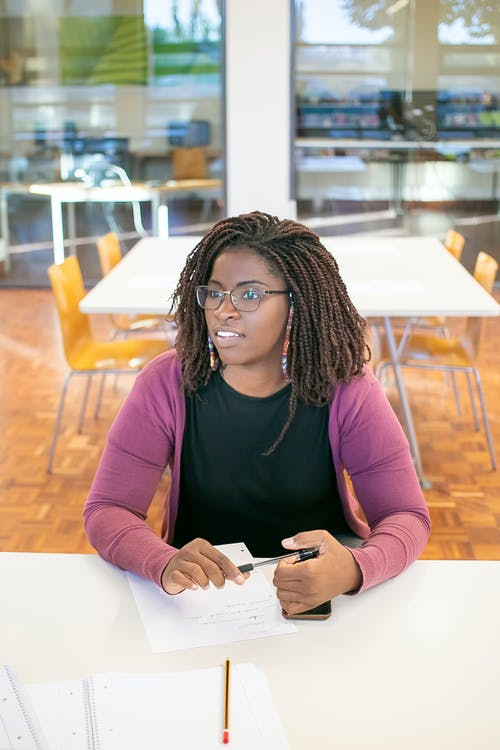 High angle of positive African American female in eyeglasses with pen and documents with cellphone sitting at table in university
