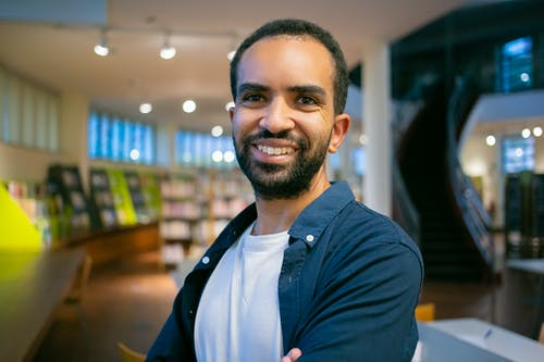 Smiling ethnic bearded student with toothy smile standing against bookshelves in library in college