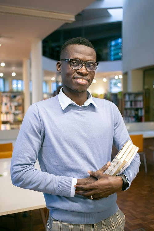 Optimistic African American man in eyeglasses with stack of books in hands standing in university library