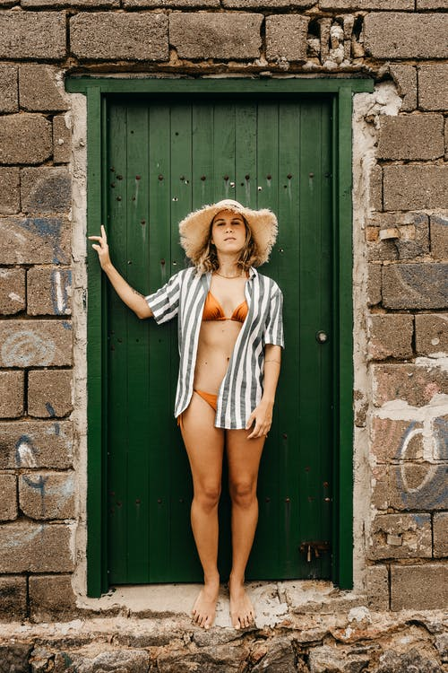 Woman in White and Blue Stripe Dress and Brown Hat Standing in Front of Green Wooden