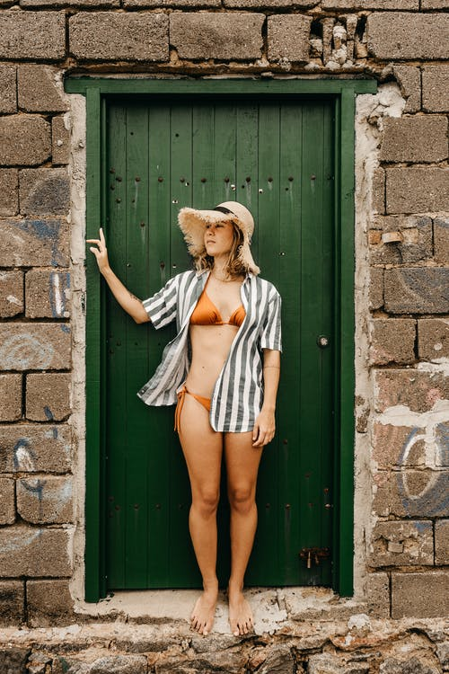 Dreamy tourist in swimwear near door of aged construction