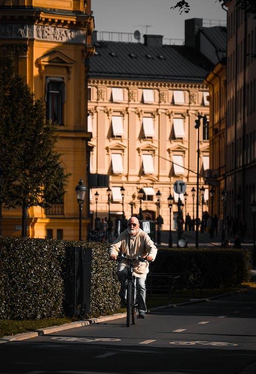 Man in White Shirt and Black Pants Walking on Sidewalk