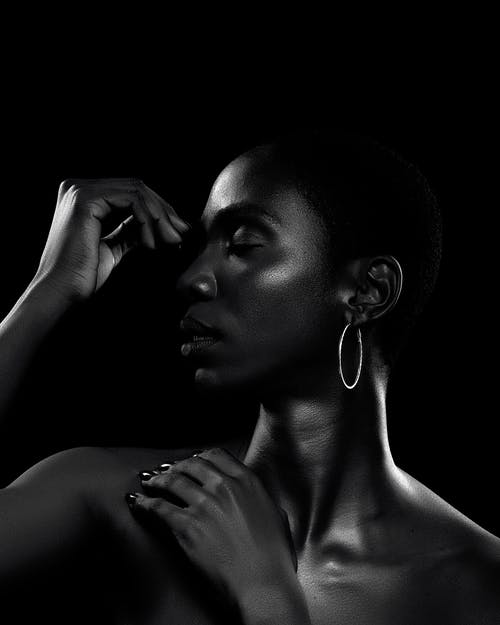Black and white African American female with closed eyes touching bare shoulders against black background