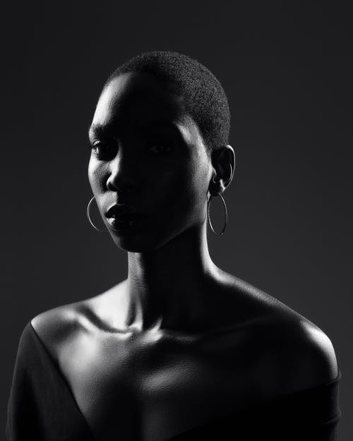Calm black woman with bare shoulders against dark background