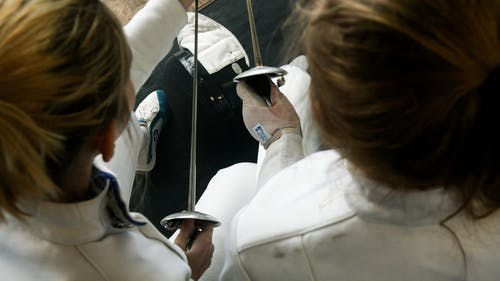 Two Women In White Uniforms Holding Swords For Fencing