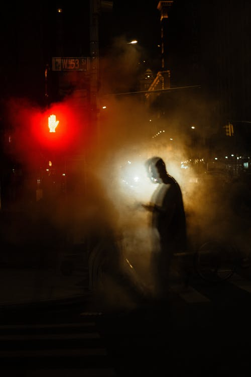 Full length of unrecognizable pedestrians silhouettes walking in white steam on asphalt road on crosswalk near sidewalk and buildings in city district at night