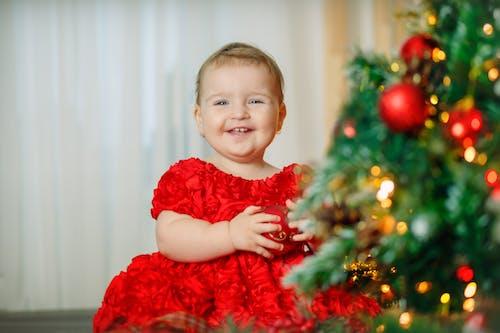 Girl in Red Dress Standing Beside Christmas Tree